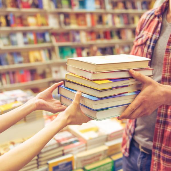 Woman handing books to customer at independent bookstore