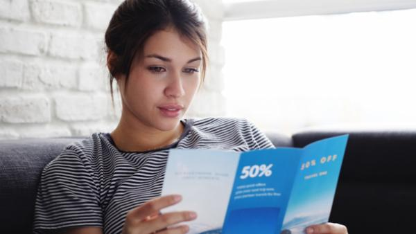 woman reading direct mail- marketing mix page