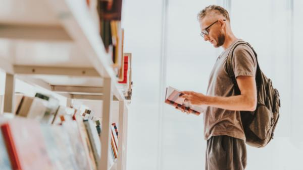 man checking book at bookstore